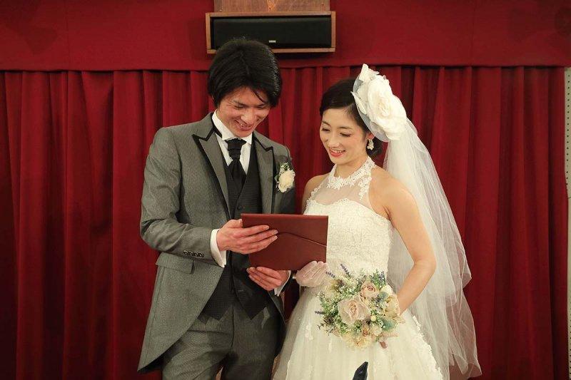 ウェディングドレス姿の女性とタキシードを着た男性が誓いの言葉を見ながら微笑んでいる写真