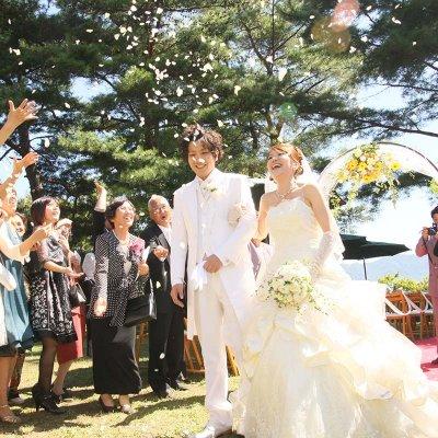 新郎新婦の退場で参列者が花道をつくって花びらをまいて祝福している様子
